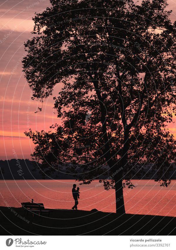 Vater und Kind bei Sonnenuntergang an einem See Sonnenuntergangssee Boot Silhouette eines Kindes rot purpur Mensch Junge Abend blau Himmel Steine Wolken