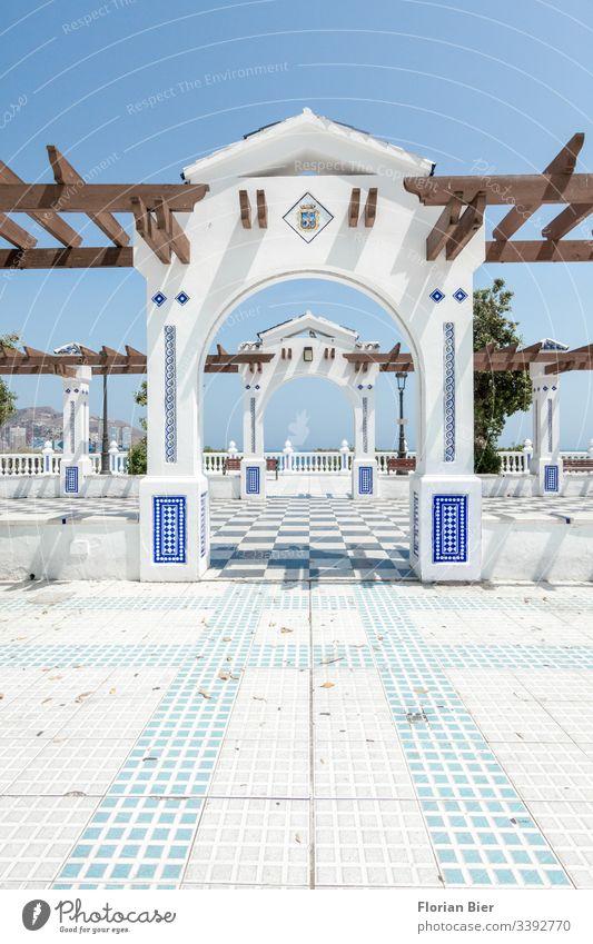 Öffentlicher Platz im Süden mit Torbogen und Mosaik Verziehrungen Holz grafisch öffentlicher Platz Muster Stadt Ausblick Tourist urban Europa Aussicht Tag blau