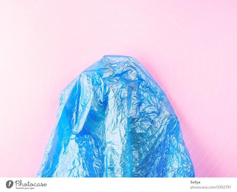 Menschliche Hand gefangen in einer Plastiktüte auf rosa Hintergrund. Konzeptionelle Flachlegung Kunststoff Meer Verschmutzung Metapher MEER Wasser blau