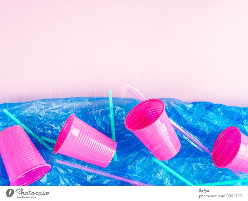 Plastikhalme und -becher im Meer, dargestellt durch eine blaue Plastiktüte. Konzept der Umweltverschmutzung. Flach auf rosa gelegt Stroh Glas Einwegartikel