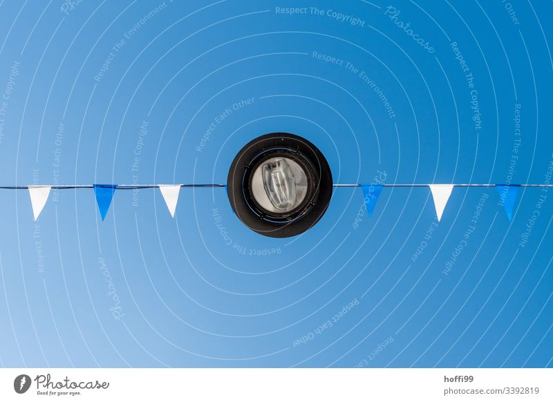 Lampe von unten mit weißen und blauen Fähnchen gegen blauen Himmel Laterne Leuchte Fahne Straßenbeleuchtung minimalistisch Blauer Himmel Blauer Hintergrund