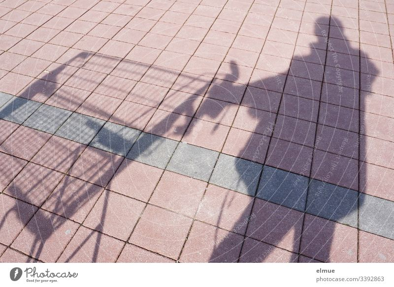 Schattenperson mit Einkaufswagen Schattenspiel Person kaufen Sonnenlicht Tag Menschenleer Farbfoto Parkplatz Kacheln Quadrat Perspektive Plan Oberfläche Spaß
