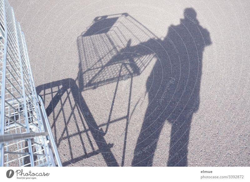 Schattenperson mit Einkaufswagen Schattenspiel Person kaufen Sonnenlicht Tag Menschenleer Farbfoto Parkplatz Perspektive Plan Oberfläche Spaß lustig