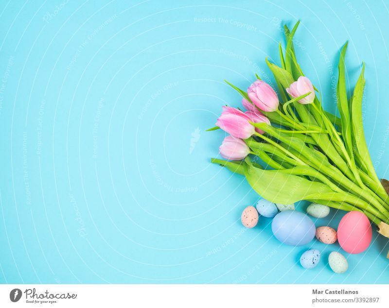 Blumenstrauß aus Tulpen und Ostereiern auf blauem Hintergrund Kopierfläche. Raum links Draufsicht Frau Frauentag Muttertag Valentinstag Frühling Valentinsgruß