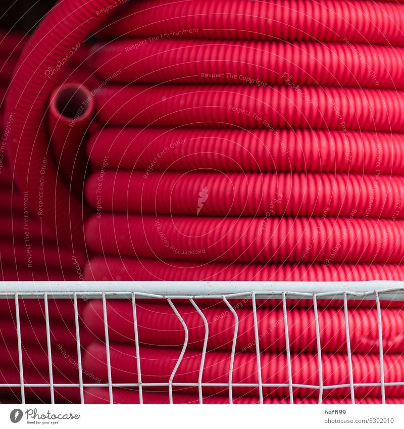 große Rolle mit rotem Flex Schlauch hinter einem deformierten Absperrgitter Schläuche Bewässerung Gehäuse PVC Röhren Abwasser Abwasserkanal Konstruktion