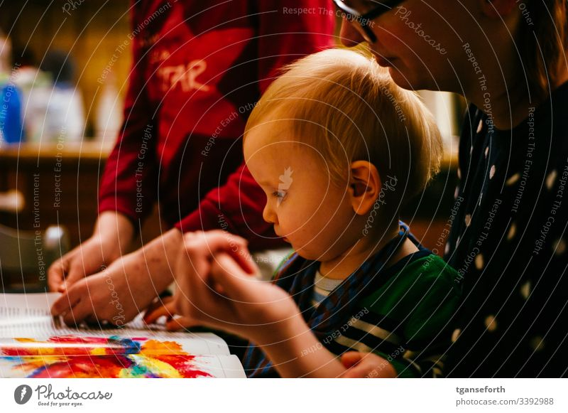kleiner Junge liest mit Mutter und Schwester eine Zeitschrift Kleinkind lernen Kind Farbfoto Kindererziehung Kindheit Schwache Tiefenschärfe Innenaufnahme