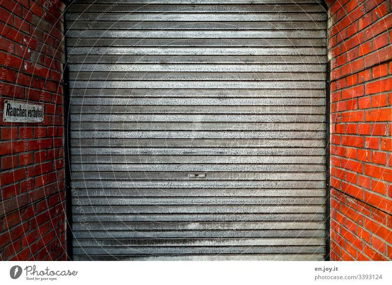Garagentor von Backsteinmauer umrahmt mit Verbotsschild rauchen verboten Lagerhalle Gebäudeteil Industrie Fabrik Tor Einfahrt Aluminium Schmutz Alt Rollladen