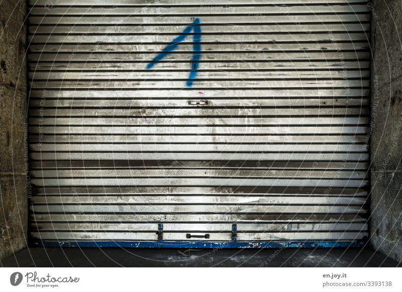 Verschmutztes Garagentor aus Aluminium Rollladen Alt Schmutz Einfahrt Tor Froschpersektive Eins 1 Zahl Graffiti Nr Nummer Erster Fabrik Industrie Gebäudeteil