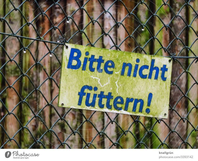Bitte nicht füttern! Maschendrahtzaun Tiergehege Hinweisschild Warnung Regentropfen schräg Aussengehege Befestigung Tierpark Zaun Verbot Wort Buchstaben