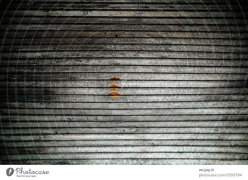 Geschlossenes Garagentor mit einem Rost Fleck Lagerhalle Gebäudeteil Industrie Fabrik Tor Einfahrt Aluminium Schmutz Alt Rollladen Licht Schatten Muster Dreck