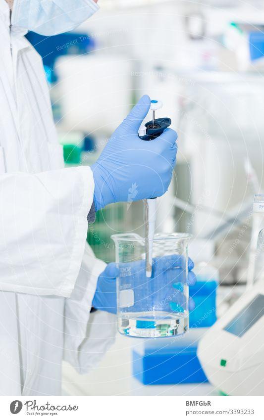 Person im Labor mit Mundschutz und Handschuhen arbeitet mit Flüssigkeit Gesundheitswesen Krankenhaus Arzt Chirurg Medikament professionell Spezialist Gerät
