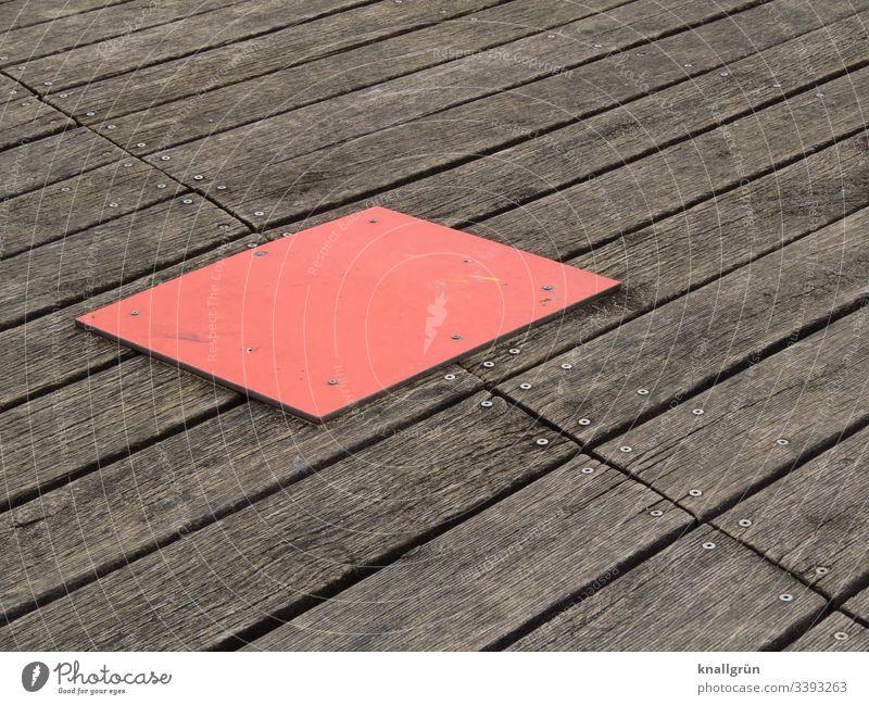 rote rechteckige Abdeckplatte auf geschraubten Holzbodenbrettern Holzbrett braun Strukturen & Formen Menschenleer Außenaufnahme Farbfoto Tag Muster Maserung