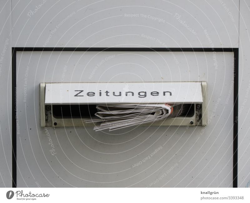 Tageszeitung in einem Haustürbriefkasten mit der Beschriftung Zeitungen steckend Briefkasten Briefkastenschlitz Außenaufnahme Farbfoto Menschenleer Tür