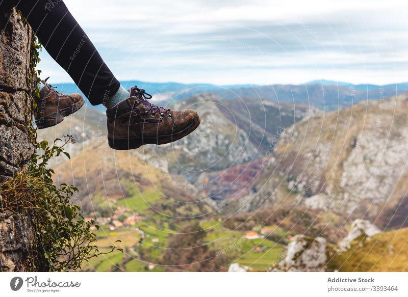 Reisende genießen die Landschaft, während sie am Rande eines Felsens im nebligen Hochland sitzen Reisender Klippe Berge u. Gebirge Trekking Aussichtspunkt
