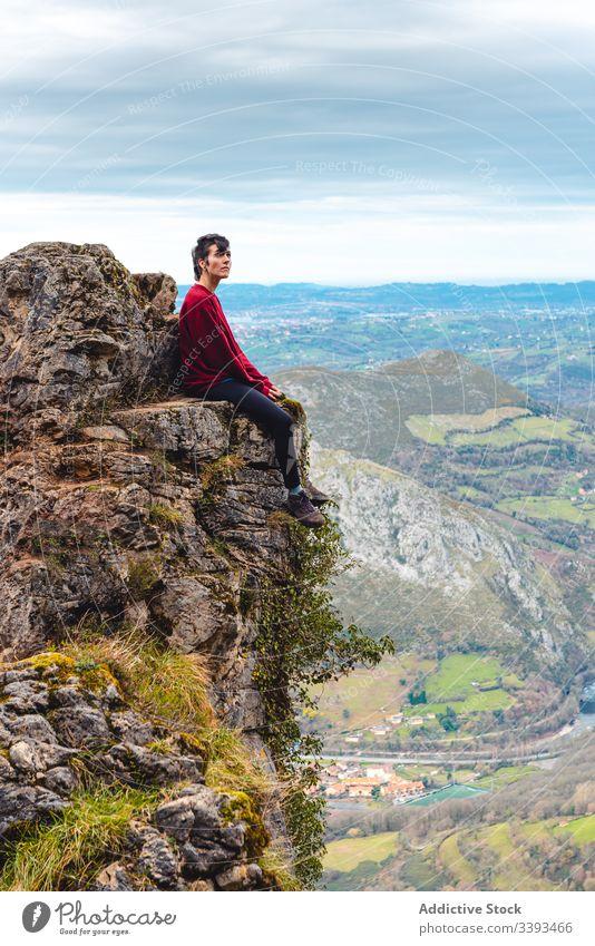 Reisender genießt Landschaft, während er am Rande eines Felsens gegen nebliges Hochland sitzt Klippe Berge u. Gebirge Trekking Aussichtspunkt Freiheit Höhe Saum