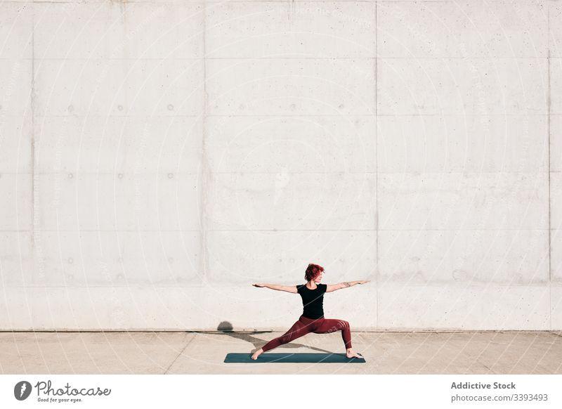 Frau macht Krieger-Zwei-Yoga-Pose auf der Straße Dehnung üben Asana Training Übung beweglich Athlet Windstille gymnastisch Beton urban Wellness Wohlbefinden