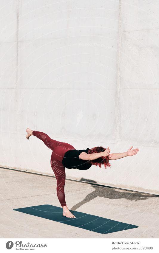 Frau macht Gleichgewichtsübung in Baumhaltung während sie Yoga auf der Straße praktiziert Athlet üben Training Übung Dehnung Barfuß Beton Windstille passen