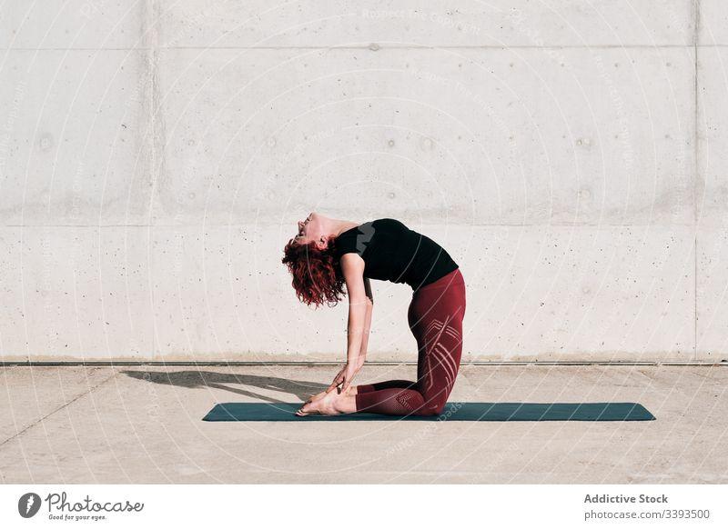 Frau macht Yoga in Kamelpose auf der Straße Dehnung üben Asana Training Übung beweglich Athlet Windstille gymnastisch Beton urban Wellness Wohlbefinden