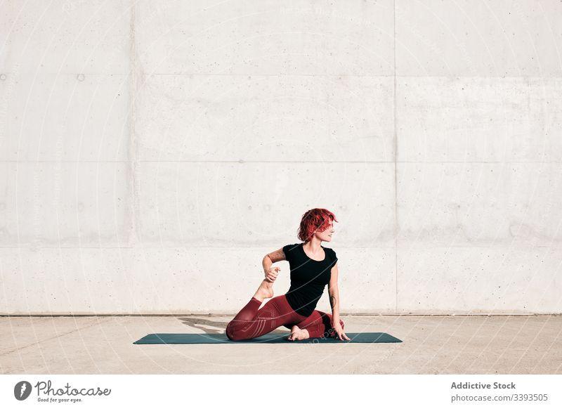 Flexible barfüßige Frau, die beim Training auf der Straße ihren Körper in gefesselter Schwanenhaltung dehnt Dehnung Yoga beweglich gebundene Schwanenhaltung
