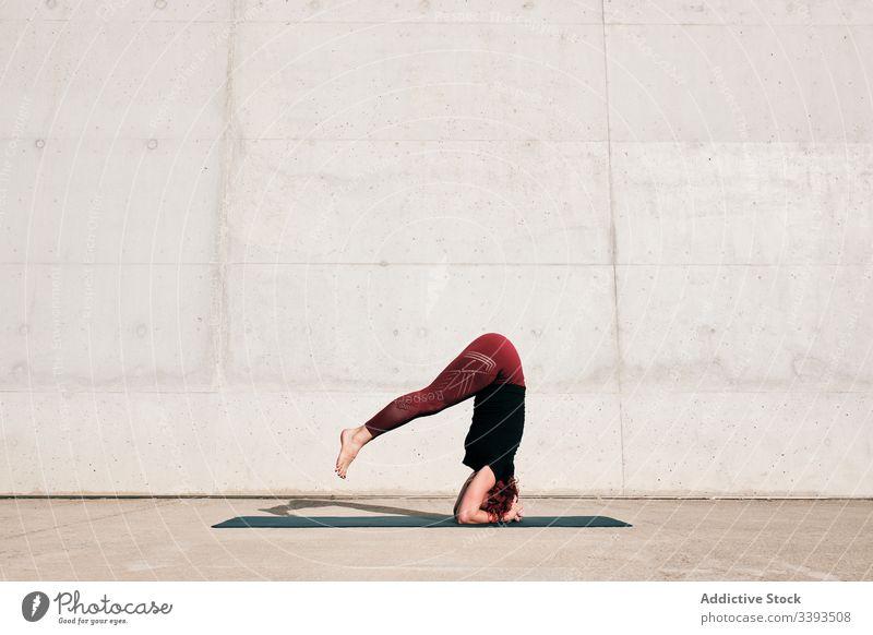 Frau macht Gleichgewichtsübung im Kopfstand, während sie Yoga auf der Straße praktiziert Übung akrobatisch üben Training urban sirsasana Beton stark beweglich
