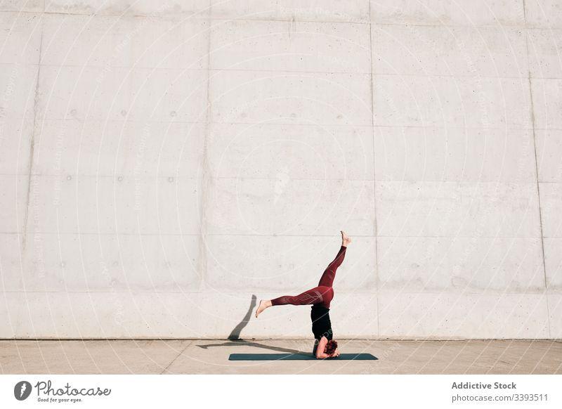 Frau macht Gleichgewichtsübung im Kopfstand mit geteilter Pose während sie Yoga auf der Straße praktiziert Übung akrobatisch üben Training urban sirsasana Beton