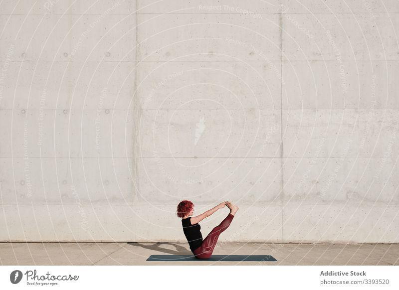 Flexible junge Sportlerin praktiziert Yoga im Gleichgewicht paripurna navasana auf der Strasse Straße Boot-Pose beweglich Übung Dehnung Frau akrobatisch üben