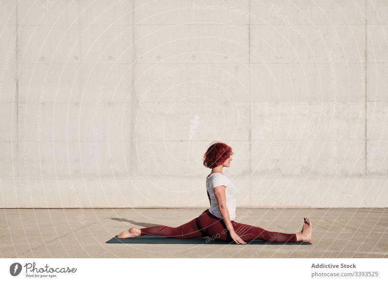 Flexible junge Sportlerin, die auf der Straße Yoga praktiziert beweglich Übung Dehnung Frau akrobatisch üben Training gymnastisch Schatten physisch urban