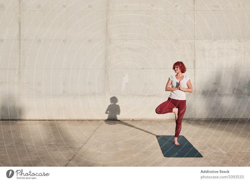 Frau macht Gleichgewichtsübung in Baumhaltung während sie Yoga auf der Straße praktiziert Athlet Namaste meditieren üben Training Übung Dehnung Barfuß Beton