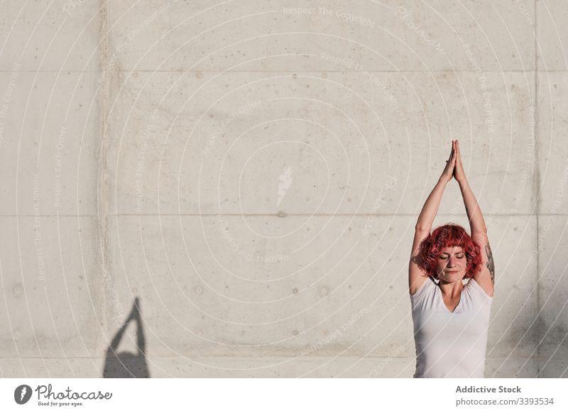 Frau in Baumpose praktiziert Yoga auf der Straße Athlet Baumhaltung Gleichgewicht Namaste meditieren üben Training Übung Dehnung Beton Windstille vrikshasana