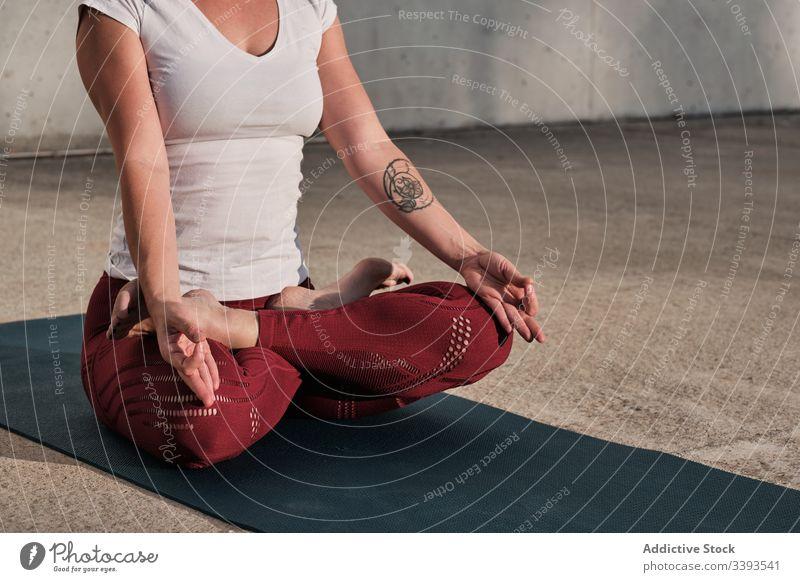 Anonyme Frau meditiert in Lotus-Pose auf der Straße meditieren Yoga ruhig üben gyan mudra beweglich idyllisch gymnastisch Athlet padmasana Barfuß Beton Übung