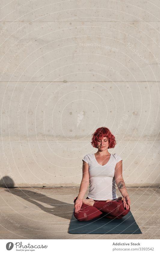 Frau mit geschlossenen Augen meditiert in Lotus-Pose auf der Straße bei Sonnenuntergang meditieren Yoga ruhig üben gyan mudra beweglich idyllisch gymnastisch