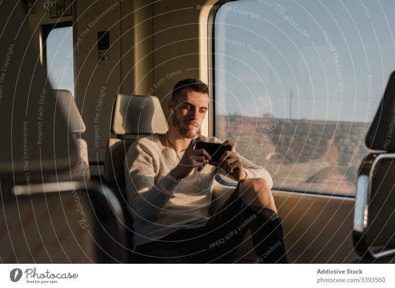 Junger männlicher Fahrgast benutzt Smartphone in der U-Bahn Passagier benutzend Mann Drahtlos Kopfhörer Textnachrichten Funktelefon anlehnen zuhören Musik Zug