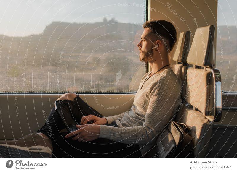 Konzentrierter männlicher Passagier mit Laptop im Zug benutzend Mann Drahtlos Kopfhörer Tippen Reise U-Bahn sonnig Mitteilung Anschluss Kontakt Information