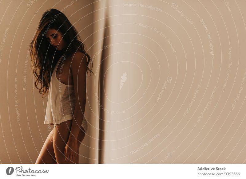 Charmante schlanke Frau in Unterwäsche an der Wand sinnlich verführerisch Frauenunterhose Tanktop Verlockung anhaben Raum feminin Frisur lässig Dessous Angebot