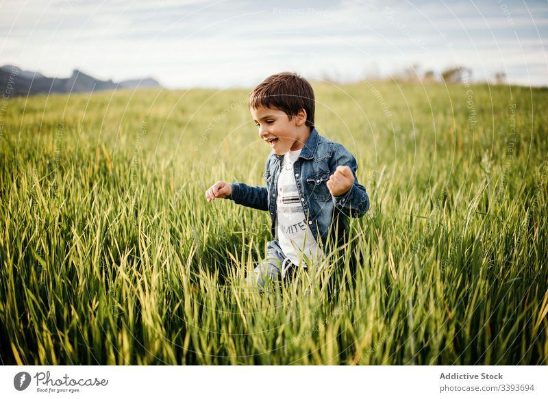 Glücklicher Junge genießt grüne Wiese auf dem Land Feld Landschaft laufen Gras Spaß spielerisch genießen hoch ländlich Freiheit wolkig Spaziergang Kind Natur