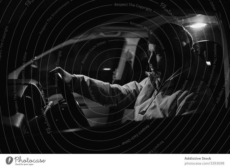 Fokussierter Mann fährt nachts Auto Laufwerk PKW Nacht Lenkrad Mitfahrgelegenheit Fahrzeug Verkehr reisen Reise männlich Kontrolle Straße Geschwindigkeit modern
