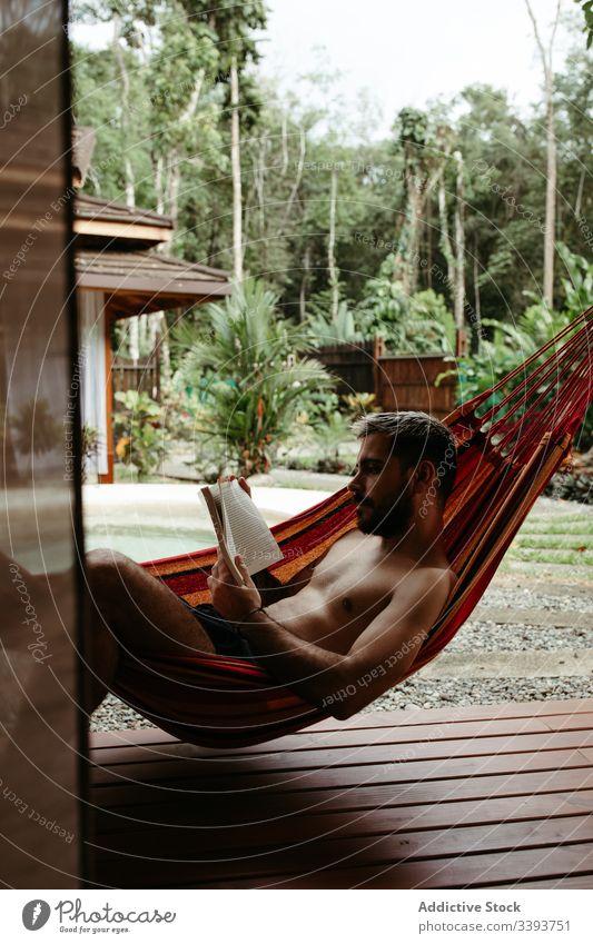 Junger männlicher Tourist in Bademode mit Buch auf Hängematte Mann Resort Hotel räkeln Kälte Beckenrand lesen exotisch tropisch Badeanzug sich[Akk] entspannen
