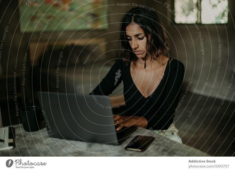 Fokussierte junge Frau benutzt Laptop im Raum benutzend Tippen Mitteilung Anschluss Internet online Surfen Browsen Gerät Apparatur freiberuflich Arbeit