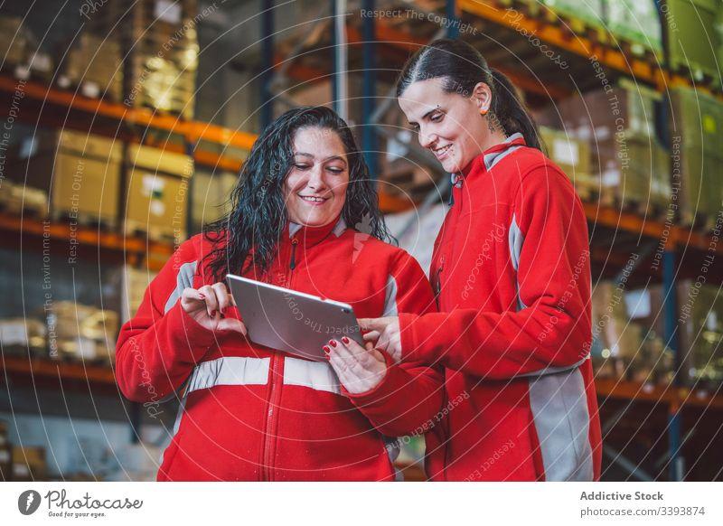 Zufriedene kluge Kolleginnen beim Surfen auf dem digitalen Tablet Lagerhalle Frauen Kollege benutzend Tablette Browsen Suche zuschauen Gerät Lächeln genießen