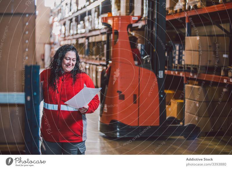 Zufriedene Dame in großem modernen Lagerhaus Lagerhalle Paket Unternehmen Frau Job lesen Schriftstück Kasten Produkt Versand Dienst Lächeln Information