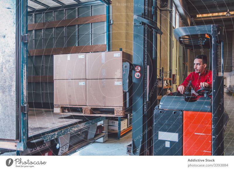 Männlicher Arbeiter einer Logistikfirma in einem Gabelstapler Mann Fahrer Stapler Versand PKW Lager Lagerhalle Maschine Gerät modern Betreiber männlich Dienst