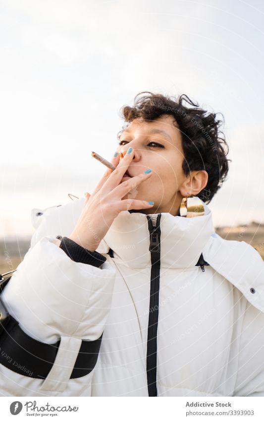 Stilvolle ethnische Teenagerin mit Zigarette Frau Rauch cool Natur warme Kleidung stumpf Nikotin provokant lässig jung Jacke Hipster Stoff Accessoire Ohrringe