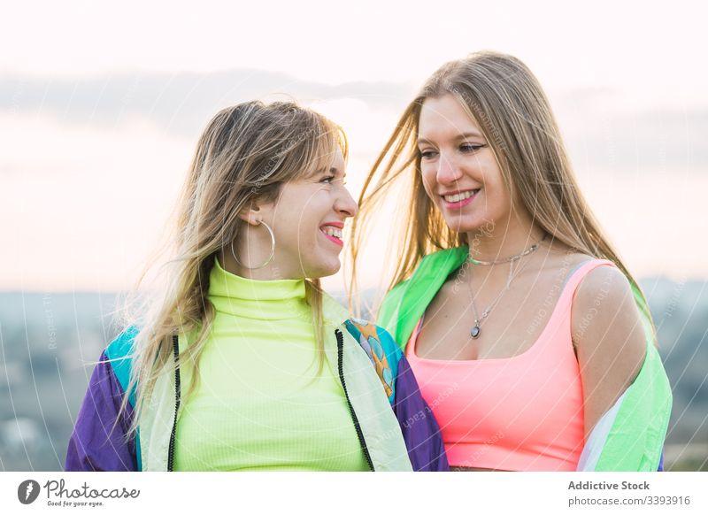 Coole moderne Frauen plaudern auf ländlichem Feld Hipster Teenager Freundin farbenfroh cool Menschengruppe anhaben Kleidung auflehnen Lächeln Lachen genießen