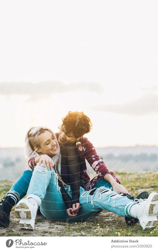 Zufriedene weibliche Teenager, die sich auf Gras umarmen Frauen Freundin Lachen Spaß Umarmung Natur Wiese bester Freund Umarmen Lächeln genießen teilen lässig