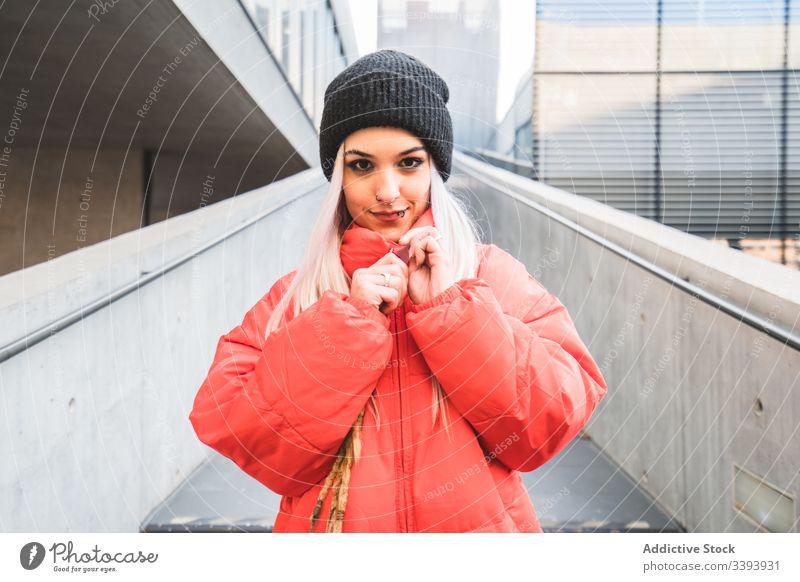 Zeitgenössische Frau in trendigem warmen Mantel auf der Straße Großstadt trendy warme Kleidung Hipster blond modern lässig Stil urban Treppe Hut Lifestyle