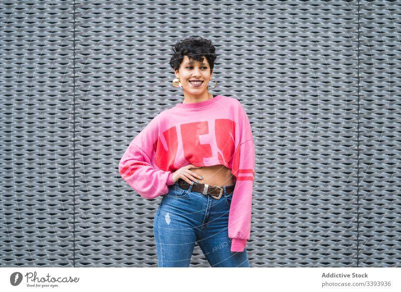 Junge ethnische Teenagerin in trendiger bunter Kleidung auf der Straße Frau Stil trendy tausendjährig farbenfroh Inhalt Stoff anhaben Körperhaltung