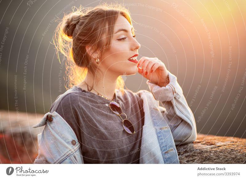 Stilvolle Frau in lässiger Kleidung erfreut sich am Anblick Lächeln genießen Sonne trendy Lifestyle Harmonie Mode ruhen sich[Akk] entspannen Outfit Wochenende