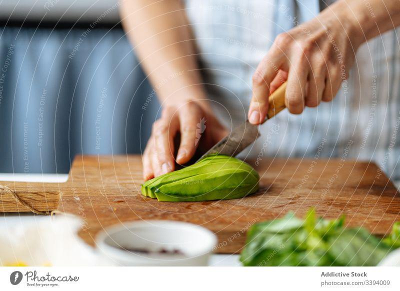 Frau schneidet Avocado auf Schneidebrett Lebensmittel Essen zubereiten Messer Schneiden Rezept Gemüse Bestandteil hinzufügen Gesundheit grün Küche Mahlzeit