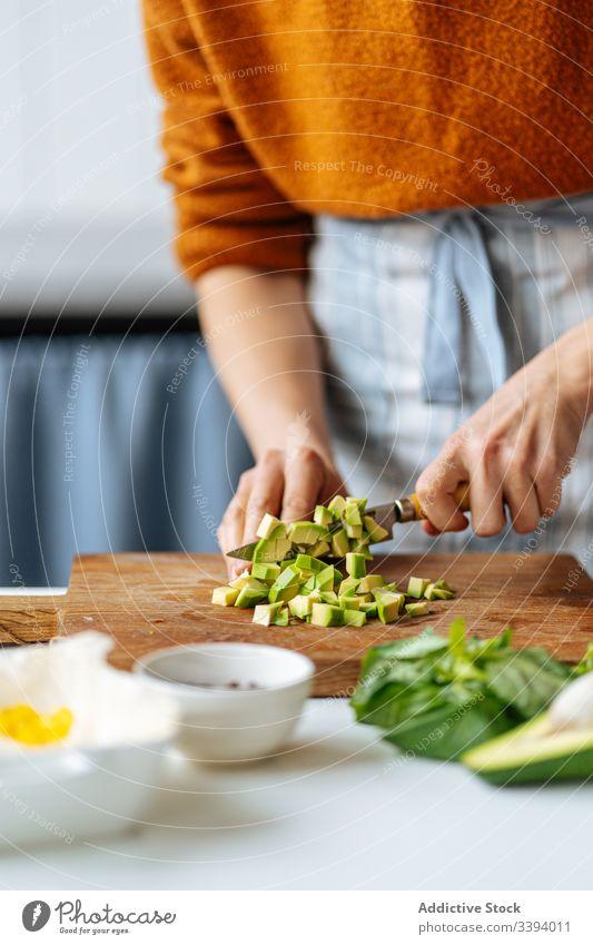 Frau schneidet gehackte Avocado auf Schneidebrett Lebensmittel Essen zubereiten Schneiden Rezept Gemüse Bestandteil hinzufügen Gesundheit grün Küche Mahlzeit