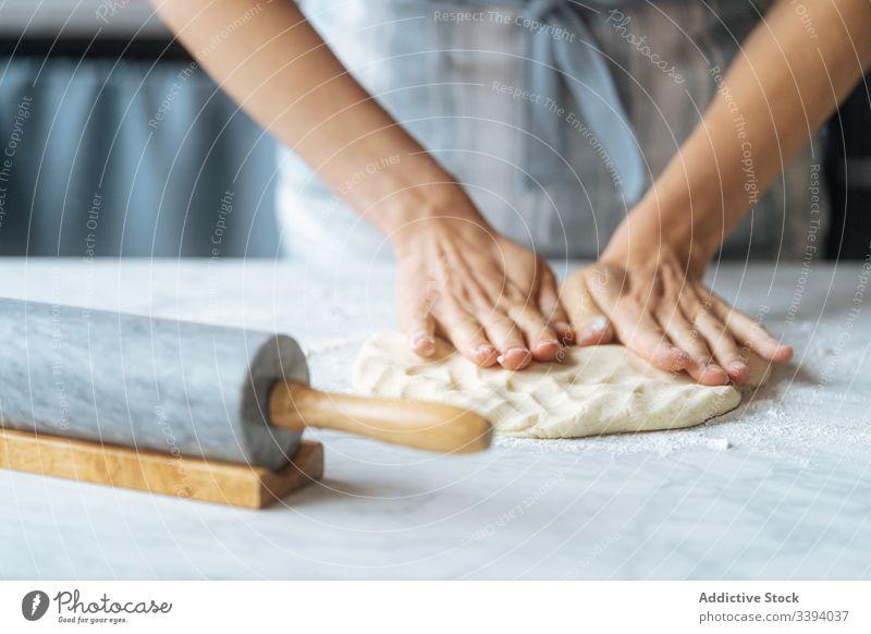 Teig kneten mit der Hand auf dem Tisch kochen Koch Kneten Teigwaren rollierend Stecknadel Mehl Vorbereitung Bäckerei Küche kulinarisch Herstellung backen